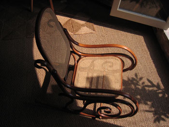 This shows the end result - the fully reconstructed rocking chair, its mahogany wood glowing and its panels beautifully recaned.