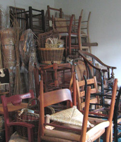 This photograph shows chairs stacked up in Sue's workshop waiting